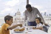 zwei Kinder und Erwachsene essen in der Küche und Bar
