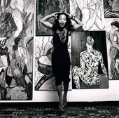 monochrome photo of artist Pacita Abad posing in front of a wall of paintings