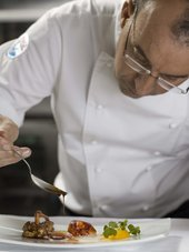 photograph of Chef Pascal Proyart presenting a plate of food