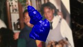 blue religious figurine floats over the top of a blurred out photograph.