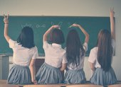 four girls in school uniforms face away from the camera