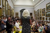 A speaker with a microphone addresses a group of people gathered sitting on the floor in the Tate Britain 1840s room.