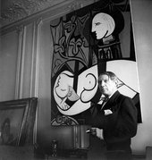Black and white photograph of Picasso stood beside a painting