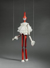 A wooden marionette puppet held up by two strings wears a red hat, a white ruffled top and red trousers