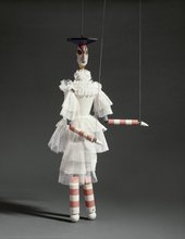 A marionette with stripey arms and legs and a white ruffled dress