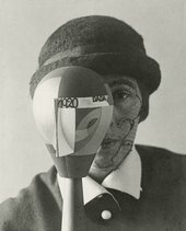 A black and white photograph where a woman faces the camera with a wooded abstract head sculpture in front of one side of her face. The woman wears a bowler hat and has face paint on the visible side of her face.