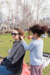 young girl cutting the hair of a woman in a park