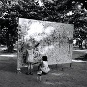 Please Draw Freely, situated outside in a woods a large wooden board is drawn on by two small children
