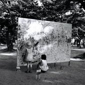 Two children drawing on a big wooden board in a park