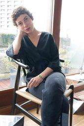 Portrait of Rosalind Nashashibi sitting in a chair
