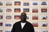 landscape photograph showing the artist Steve McQueen in front of his Year 3 project. Behind him are many framed photographs of school groups. He is wearing glasses and a black jacket.
