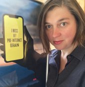 Head and shoulders of a person next to a poster showing a hand holding a phone on which is written 'I miss my pre-internet brain'. The poster is positioned so the hand appears to belong to the person.