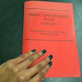 Photograph of a hand with painted nails resting on the cover of a red pamphlet titled Equal Opportunities in the New Era