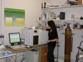 a woman stands in front of a mass spectrometer machine