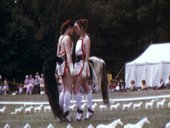 Film still showing two people standing head-to-head; they wear matching outfits featuring long white socks, pinafores and horse tails. They stand in a field with white tent and spectators, like a country fair