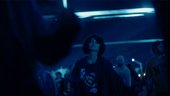 a blue-hued image of young people in a nightclub