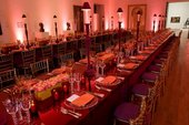 two tables set up for dining with bright pink lights