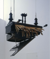 Photograph of artwork Concert for Anarchy by Rebecca Horn. A grand piano is suspended upside down from ceiling with the hammers falling out.