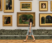 A woman walks through the 1840 gallery with paintings in the background