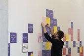 A person reaches up to add a piece of paper to a mural