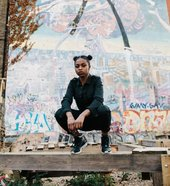 Artist Nadia Rose squatting on a gate