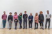 Photograph of some members of the Reshaping the Collectible project team, standing in a line against a white wall in a gallery at Tate Britain