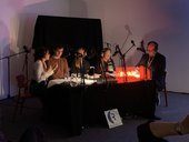 Five people sit around a table covered in microphones on stands, the room is dark and a red light glows on the table