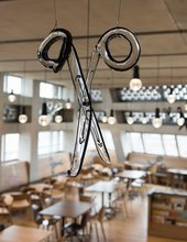 Photo of a glass scissor hanging from the ceiling