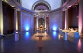 lights shine upwards in an empty gallery space with stone pillars