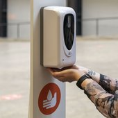 Person using a sanitiser dispenser.