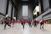 Children in school uniform run in turbine hall with placards