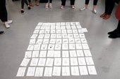 81 small pencil drawings arranged on the floor in a grid