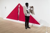 Student standing in front of a red artwork