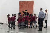 A group of children looking at an artwork with an artist