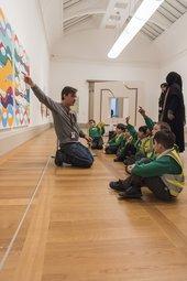 An artist speaking to children in the gallery