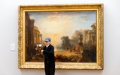 Young person using a selfie stick in front of an artwork