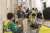 Photograph of a schools workshop at Tate Britain. Young students wearing hi-vis jackets making wooden sculptures in the gallery