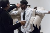 Photograph of students collaborating making cardboard wings, putting them on the back of another student during a workshop at Tate Modern