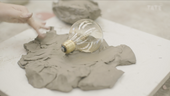 A lightbulb in a clay bed
