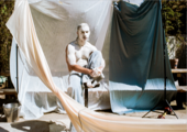 Photo of a man in white clay surrounded my hanging sheets