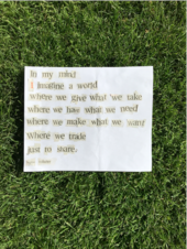 paper on grass with text reading 'land and us'
