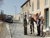 people stand in army uniform outside a house