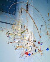 A colourful sculpture made up of cheap everyday objects in a spiral shape resembling DNA.