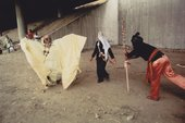still from film showing three people in big costumes posing in derelict concrete area