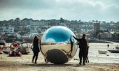 People roll a large silver ball on St Ives' Harbour Beach