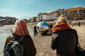 Two people watch as a large silver ball is moved across the sand at St Ives' Harbour beach