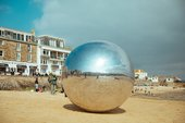 A large silver ball sits on the sand of St Ives' Harbour Hotel in the sunshine