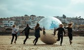 People chase a large, silver ball across the sand of St Ives' Harbour Beach