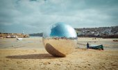 The large silver ball from special performance 063 Urban Songline (Another Hurling of the Silver Ball) by Allard Van Hoorn sits on St Ives' Harbour Beach