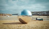 Photograph of the large silver ball from special performance 063 Urban Songline (Another Hurling of the Silver Ball) by Allard Van Hoorn sits on St Ives' Harbour Beach